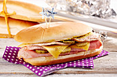 Hot Dog Brötchen mit Schinken, Essiggurken, Käse, kaltem Schweinebraten und Senf