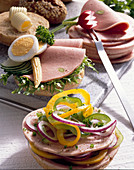 Sausage sandwiches with cucumber, onion rings and peppers, or with cucumber, egg and sweetcorn