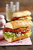Baguettes with chicken schnitzel, salad, remoulade sauce and tomato