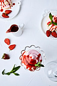 Small strawberry pavlovas drizzled with strawberry sauce