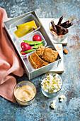 Lunchbox mit Crackern, Dips, Gemüse und Obst