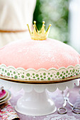 A pink princess cake on a cake stand