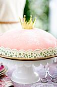 A pink princess cake on a cake stand