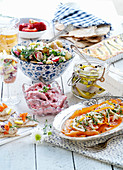 a buffet with potato salad, herring salad, smoked salmon and crispbread