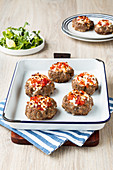 Minced meat nests filled with a tomato and sheep's cheese topping