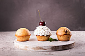 Muffins and cupkake with whipped cream decorated with cherry
