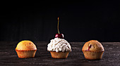 Muffins and cupcake with whipped cream decorated with sweet cherry