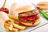 A burger with spicy ketchup sauce and french fries