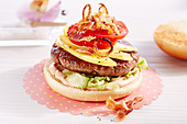 Caribbean burger with fried onions, bacon, chili, pineapple and mango