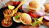 Grilled salmon burgers with onion, tomato, lemon, mayonnaise, egg and rocket