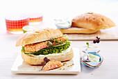 Sesame salmon burger with wasabi cream, salad and radish cress