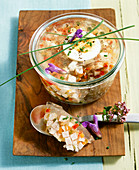 Roast pork brawn in a mason jar with boiled eggs, chives and flowers