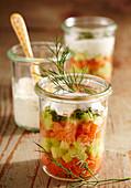 Layered salad in mason jars with smoked salmon, cucumber, dill, yoghurt, lemon, olive oil and horseradish