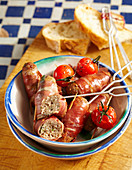 Minced meat and sage rolls with serrano ham, sherry tomatoes and white bread (Spain)