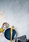 Blue dessert plate with golden cutlery, salt, pepper and Christmas decorations
