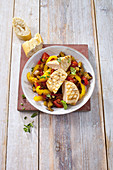 Chicken fillet on a bed of colourful vegetables