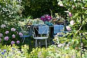 Gedeckter Tisch im Garten mit Strauß aus Pfingstrosen, Rosen und Dahlien