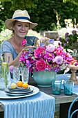 Frau steckt Frühsommerstrauß mit Pfingstrosen, Rosen und Dahlien