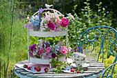 Etagere mit Rosen, Malven, Ringelblume, Rittersporn, Witwenblume, Phlox, Glockenblumen, Staudenwicke und Knorpelmöhre als Tischdekoration