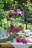 Etagere mit kleinen Sträußen aus Rosen, Wiesenkerbel, Witwenblume, Frauenmantel und Lupine als Tischdekoration