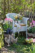Korbsessel mit Frühlingsstrauß zwischen Kübeln mit Frühlingsbepflanzung am Gartenzaun österlich dekoriert