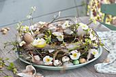 Osterkranz aus Zweigen, dekoriert mit Primelblüten, Eierschalen, Federn und Steckzwiebeln