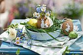 Osternest mit bemalten Ostereiern, Sträußchen aus Vergißmeinnicht, Erdbeerblüten, Primel und Gänseblümchen