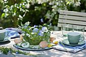 Ostertischdeko auf der Terrasse mit Hornveilchen, Gräsern, Ostereiern und Kerze