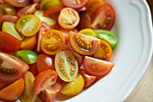 Colourful tomatoes, halved and quartered, on a plate