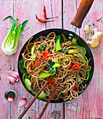 Soba noodles with pak choi in a wok