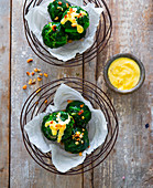 Spinach balls with hollandaise sauce and pine nuts