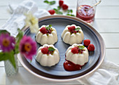 Vegan coconut and yoghurt panna cotta in tartlet shapes with raspberry sauce