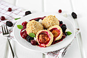Damson dumplings in a pool of berry sauce
