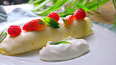 Stuffed crepes with cream, strawberries and raspberries being made