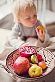 Boy taking fruit from bowl