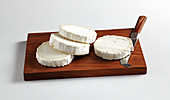 Sliced round goat's cheese with a cheese knife on a kitchen board