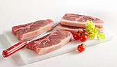 Raw pork shoulder in four slices (lumberjack steaks)
