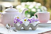 Ei als Vase mit Hornveilchen und Margariten, dahinter ein Teegedeck