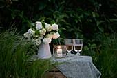 Schneeball in einer weißen Kanne, daneben Weingläser und ein Windlicht