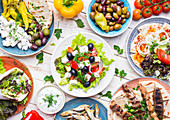 Greek food: Meze, gyros, souvlaki, fish, pita, greek salad, tzatziki, assortment of feta, olives and vegetables