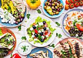 Greek food: Meze, gyros, souvlaki, fish, pita, greek salad, tzatziki, assortment of feta, olives and vegetables