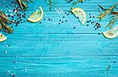 Blue coloured rustic wooden background, lemon slices, herbs, pepper, sea salt