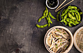 Chinese dumplings in rustic wooden bamboo steamer with green boiled soybeans edamame, soy sauce and chopsticks