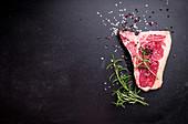 Raw marbled meat steak with seasonings on black chalkboard background