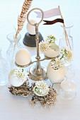 Eierschalen auf Drahtfüßen als Vasen für weiße Blümchen