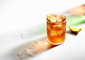 Ice cold iced tea with lemon wedges, drips on glass, colored shadows and melted ice
