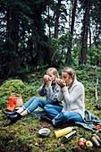 Zwei Frauen essen Suppe beim Picknick im Wald