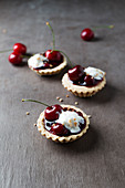 Tartlets with cherries, cream and red groats