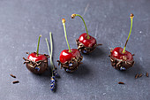 Cherries with chocolate, chocolate sprinkles, lavender flowers and gold powder