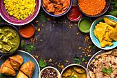 Verschiedene indische Gerichte auf dunklem Holzuntergrund